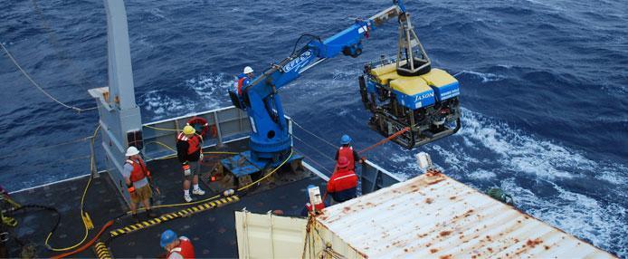 Ship crane lowering equipment into the ocean